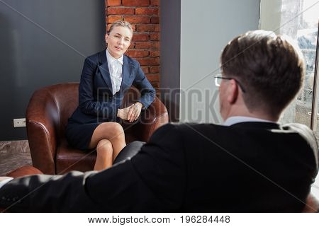 Businesspeople in formal suit sitting in armchair and making negotiates at office.