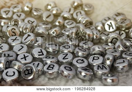 The discarded alphabet of beads on cloth