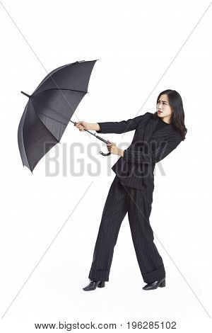 young asian businesswoman holding a black umbrella studio shot isolated on white background.