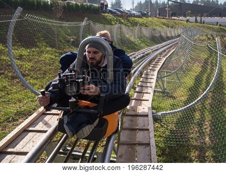 young videographer with gimball video slr at work on alpine coaster