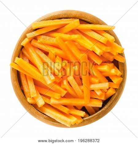 Carrot sticks in wooden bowl. Fresh cut crisp strips of Daucus carota, a root vegetable with orange color. Edible taproot pieces. Isolated macro food photo close up from above on white background.