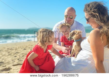Family of four with kids on the beach, parents sitting on the sand, hugging, girls in red dress playing with the dog. Candid shot, real people.