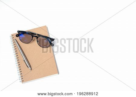 Top view of modern white office desk table with notebook pen and glasses with copy space flat lay.