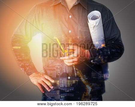 Double exposure of city and engineering holding tape measure and blueprint