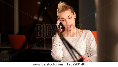 Young woman using mobile phone while working on computer at night in dark office.
