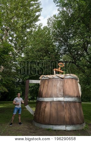 The guy holds a huge wooden mug with beer in the city park.