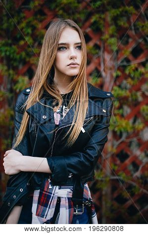 Fashion portrait pretty young woman. Long hair girl in black jacket outdoor. beautiful stylish young woman in leather jacket posing against wooden webbed fence