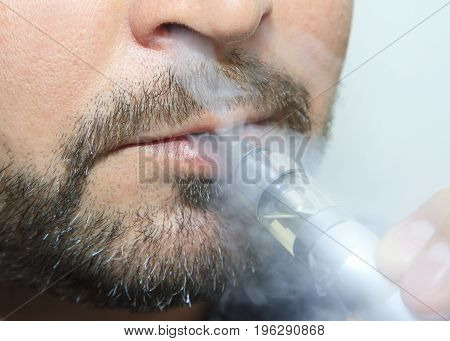 man smoking electronic sigarette with smoke close up