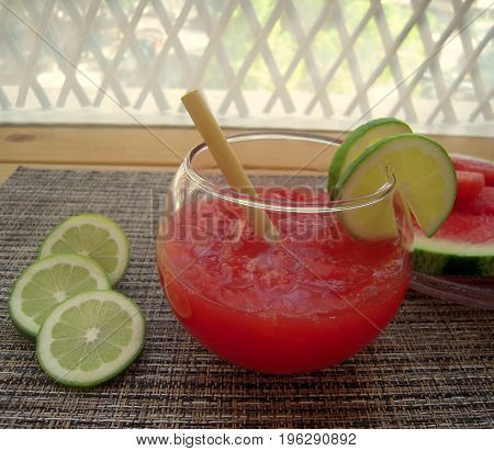 Watermelon smoothie with lime juice on the veranda table.