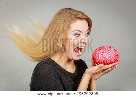 Funny face expressions fooling around concept. Crazy woman holding brain wanting to eat it