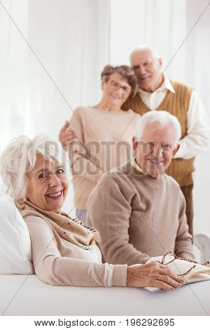 Two old couples enjoying retirement together in a day-care center