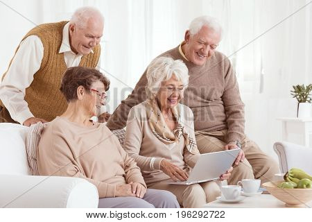 Two elderly couples excitedly looking at a laptop in a nursing home