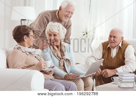 Friendly conversation of elderly neighbors drinking tee and using laptop