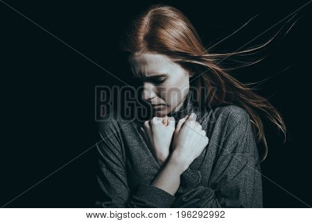 Girl clenching her fists next to her neck while feeling intense sorrow