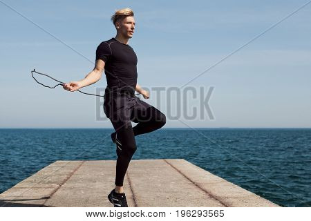 Young man in sportive outfit using jumping rope on pier during daylight.