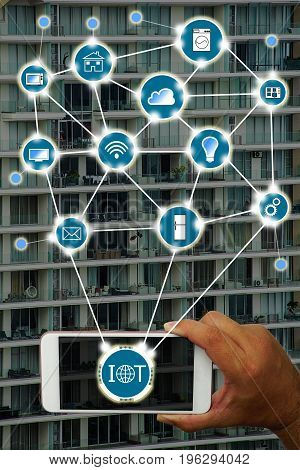 Internet of things (IOT) concept : Hand holding smartphone controlling various household equipment with building background. Smart home concept Smart Building Concept.