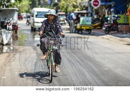 Siem Reap Cambodia March 19 2016: A woman riding a bicycle on a street in Cambodia