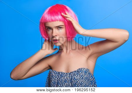 female model posing in dress and pink wig looking at camera on blue background.
