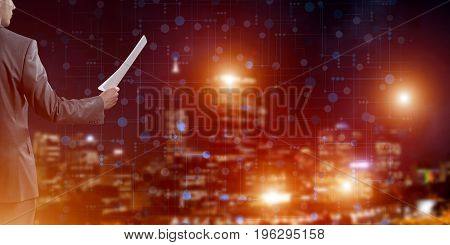 Businessman standing with back and holding contract or report in his hand
