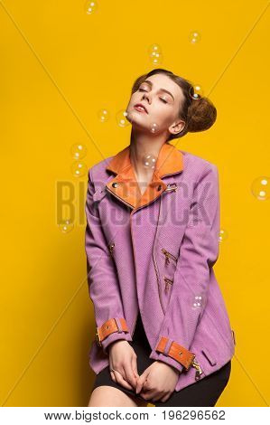 Girl wearing ping stylish jacket posing in studio on yellow background surrounded be bubbles.