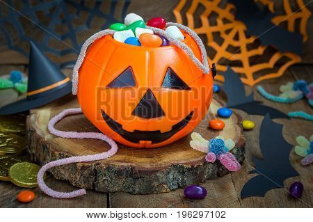 Halloween Jack o Lantern bucket overflowing with candy spooky decorations on background horizontal