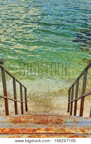 Rusty iron stairs descending into sea. Vertical orientation