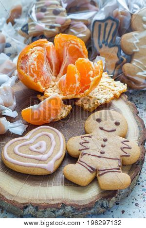 Sweet gifts for holiydays. Homemade christmas gingerbread cookies and caramel candies on wooden board vertical