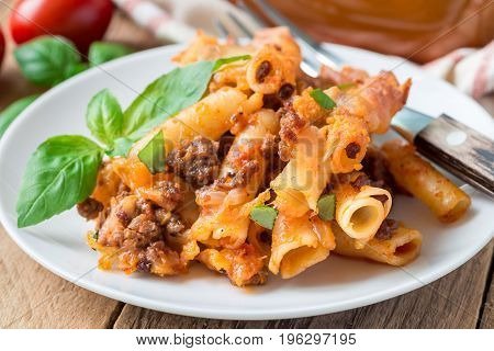 Ziti bolognese on a white plate pasta casserole with minced meat tomato sauce and cheese horizontal
