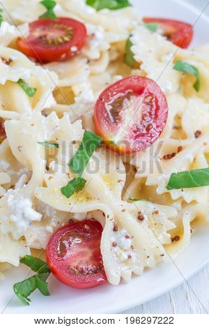 Pasta salad with tie pasta feta cheese cherry tomatoes mustard and basil vertical