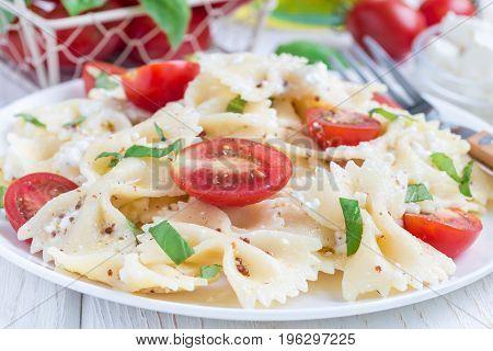 Pasta salad with tie pasta feta cheese cherry tomatoes mustard and basil horizontal