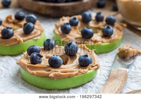 Healthy sandwich. Green apple rounds with peanut butter and and blueberries on wooden table horizontal