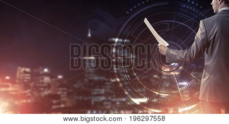 Rear view of businessman against virtual panel interface holding papers in hand