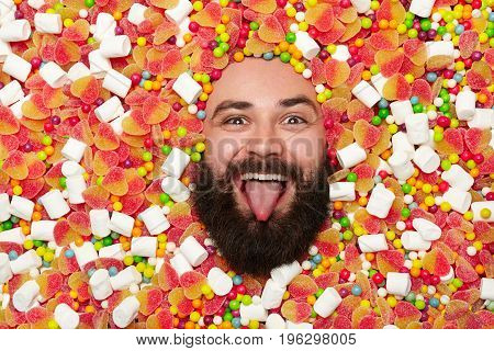Bearded funny man all covered with sweets and marshmallow putting out tongue and looking at camera.