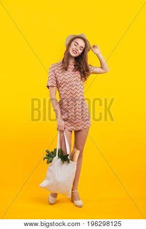 Young content girl in dress holding bag with groceries and posing with eyes closed.