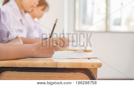 Asian girls students writing test exams on paper for Admissions in high school with uniform student in School classroom of Thailand taking exam background and education concept