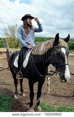 Young Man With Long Hair In Hat Riding A Horse On Countryside And Holding His Hat