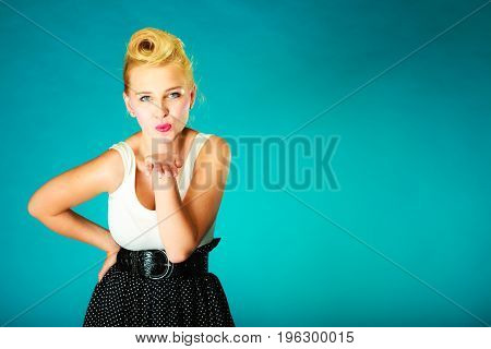 Romantic gestuers unconventional style concept. Beautiful young pin up girl sending air kisses. Studio shot on blue background.