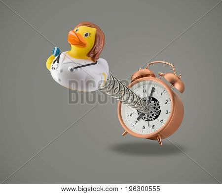 Rubber duck Doctor on spring coming out of alarm clock