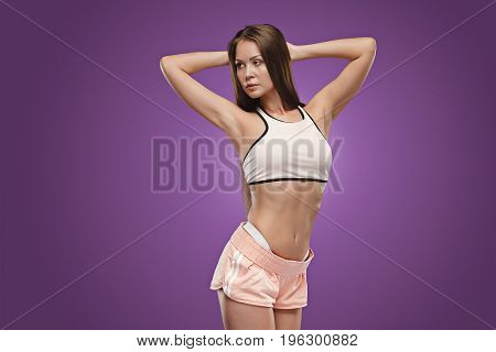 Muscular young woman athlete posing at studio on lilac background