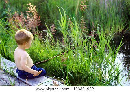 a little boy fishing in a city Park