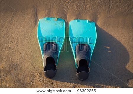 Snorkel fins on sandy beach and sea. Space for copy.