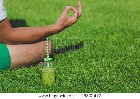 Close up of man sitting on grass in yoga lotus position. Kiwi juice in glass bottle with drinking straw next to him. Healthy lifestyle concept. Copy space.