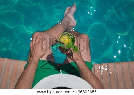 High angle view of tourist holding glass of mojito cocktail at the poolside