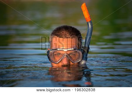 Portrait of diver wearing snorkel and goggles on water surface