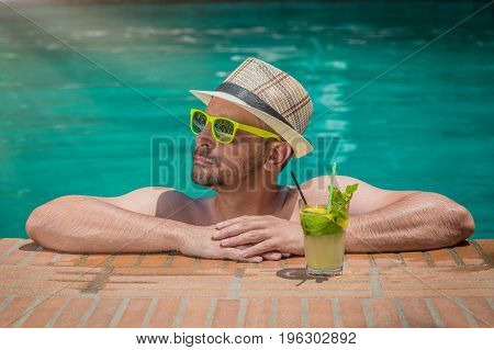 Man enjoying and relaxing in swimming pool with mojito cocktail
