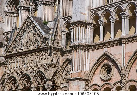 Close-up of the front facade of Ferrara Cathedral, made in various types of marble. In the city center of Ferrara, a graceful and important medieval town. Located in the Emilia-Romagna region