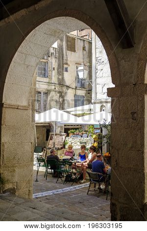 BONIFACIO CORSICA FRANCE - 15 JUNE 2017 - Looking through archway to tourists enjoying drinks outside one of the many bars in the pretty old town of Bonifacio on the Mediterranean island of Corsica.