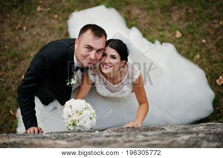 Nifty Wedding Couple Enjoying Each Other's Company Against Huge Stone Wall.