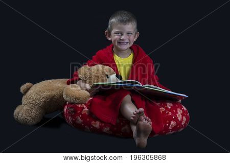 Funny boy with a teddy bear reading a book before bed time