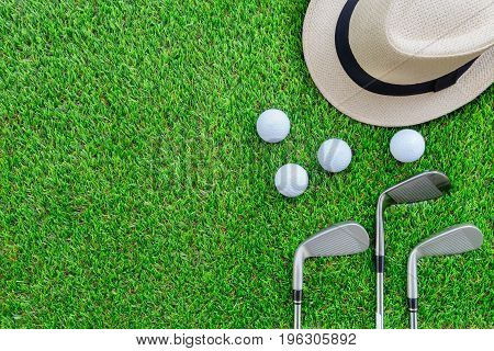 Golf concept : Panama hat, golf balls, golf iron clubs, flat lay on green glass with copy space.